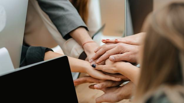 Ścieśniać. zespół biznesowy łączący ręce nad biurkiem. pojęcie pracy zespołowej