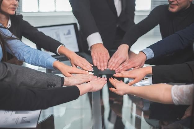 Ścieśniać. zespół biznesowy tworzący krąg z ich dłoni. pojęcie pracy zespołowej