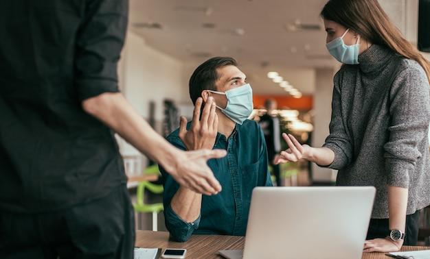 Ścieśniać. zespół biznesowy w maskach ochronnych omawiający kwestie związane z pracą.