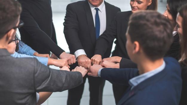 Ścieśniać. zespół młodych profesjonalistów stojących w kręgu. pojęcie pracy zespołowej