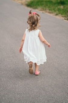 Ścieżką biegnie dziecko w białej sukience