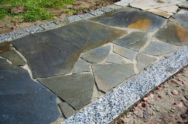 Ścieżka ogrodowa z płytami z kamienia naturalnego i obrzeżami z kostki brukowej