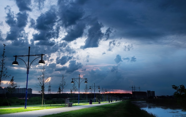 Ścieżka parku miejskiego w pobliżu rzeki z latarniami na tle nieba z deszczowymi chmurami