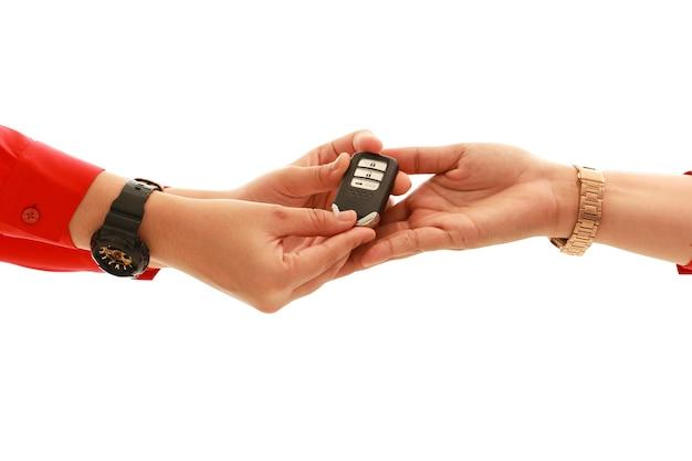 Ścieżka przycinająca ręka kobiety z czerwonej koszuli dając nowoczesny klucz od samochodu do ręki kobiet na białym tle. koncepcja przewozów. sprzedaj lub kup koncepcję.