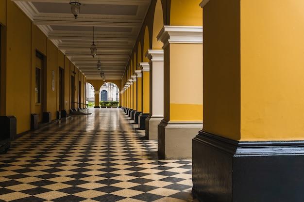 Ścieżka z czarno-białymi płytkami z żółtymi kolumnami po stronie przejścia santa rosa w historycznym centrum limy peru