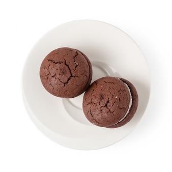 Ściska czekoladowych ciastka i śmietankę na białym talerzu odizolowywającym nad białym tłem