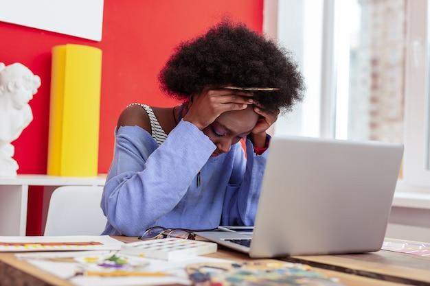Ściskając głowę. projektantka mody trzymając się za głowę, czując się skrajnie zmęczona po całym dniu pracy