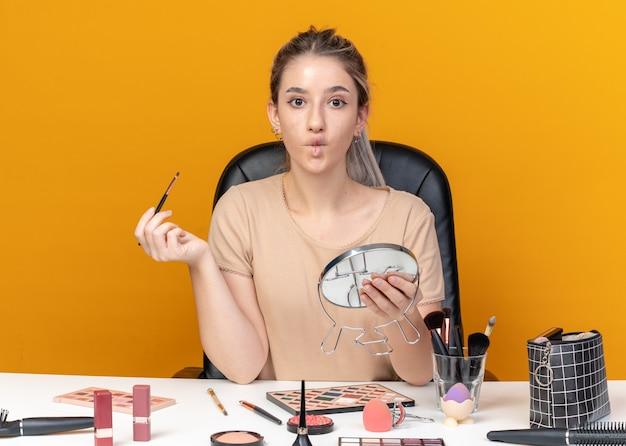 Ściskając usta młoda piękna dziewczyna siedzi przy stole z narzędziami do makijażu, trzymając pędzel do makijażu z lustrem na białym tle na pomarańczowym tle