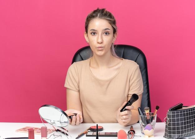 Ściskając usta młoda piękna dziewczyna siedzi przy stole z narzędziami do makijażu, trzymając pędzel do pudru na białym tle na różowym tle