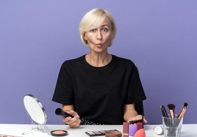 Ściskając usta młoda piękna dziewczyna siedzi przy stole z narzędziami do makijażu, trzymając pudrowy rumieniec na białym tle na niebieskim tle