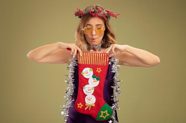 Ściskając usta młoda piękna dziewczyna ubrana w fioletową sukienkę i wieniec z okularami i girlandą na szyi, trzymając i patrząc na świąteczną skarpetę odizolowaną na oliwkowozielonym tle