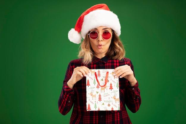 Ściskając usta młoda piękna dziewczyna w świątecznym kapeluszu w okularach trzymająca torbę na prezent na białym tle na zielonym tle