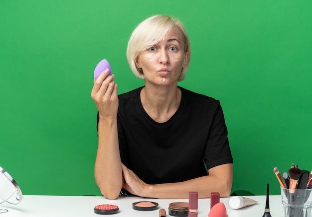 Ściskając usta mylone młoda piękna dziewczyna siedzi przy stole z narzędziami do makijażu, stosując krem tonujący, trzymając gąbkę na białym tle na zielonym tle