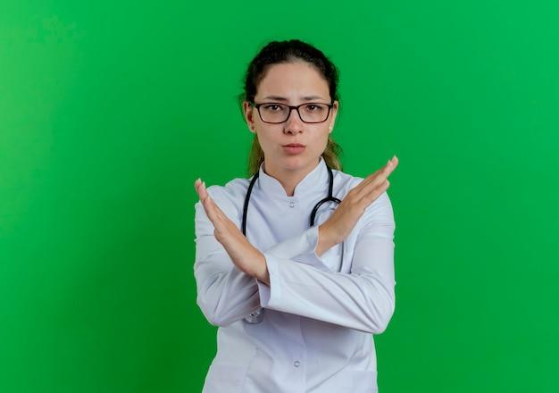Ścisła młoda kobieta lekarz ubrana w szlafrok medyczny i stetoskop i okulary nie robi żadnego gestu na zielonej ścianie z miejsca na kopię