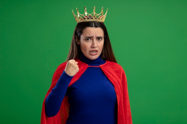 Ścisłe młoda dziewczyna superbohatera noszenie korony trzymającej pięść na białym tle na zielono