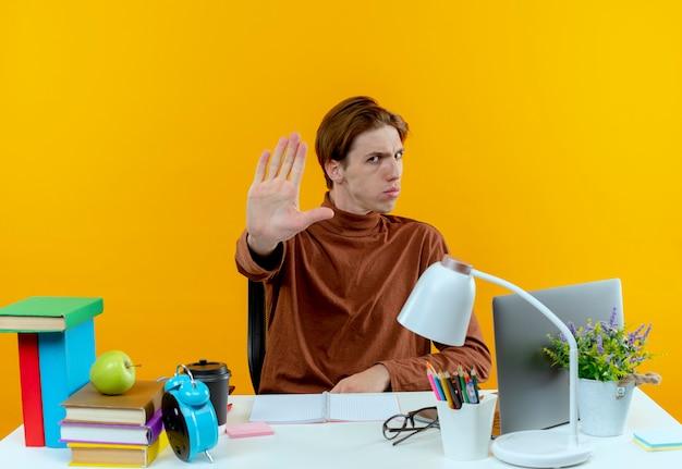 Ścisłe młody uczeń chłopiec siedzi przy biurku z narzędziami szkolnymi pokazując gest stopu na żółto