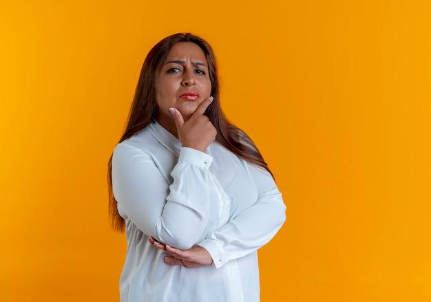 Ścisłe przypadkowe kaukaski kobieta w średnim wieku kładąc rękę pod brodą na białym tle na żółtej ścianie z miejsca na kopię