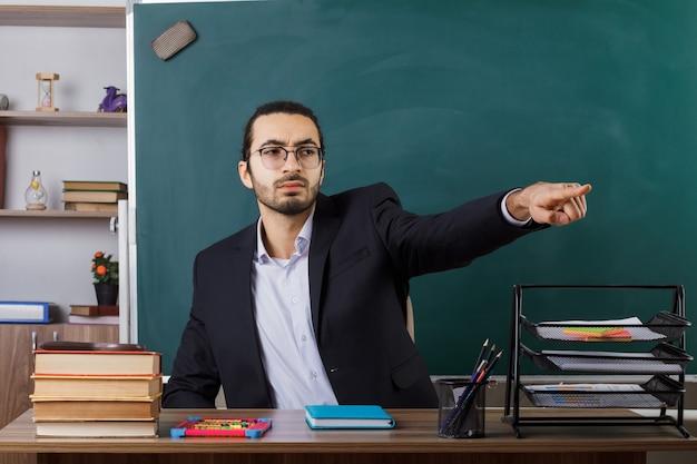 Ścisłe punkty z boku nauczyciela płci męskiej w okularach siedzącego przy stole z narzędziami szkolnymi w klasie