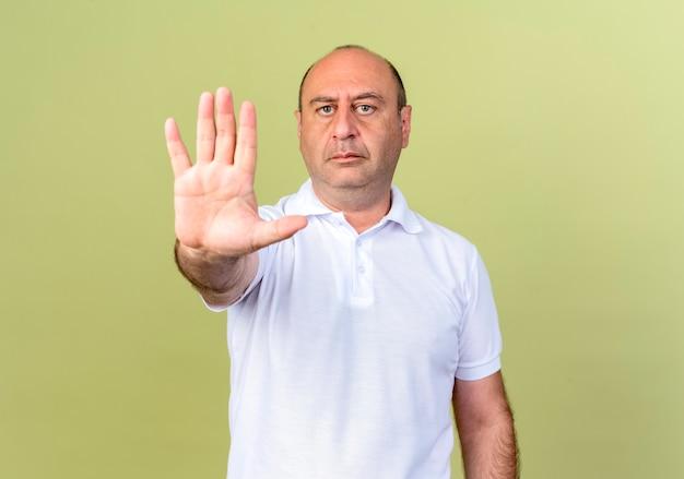Ścisły dojrzały mężczyzna pokazujący gest stopu na białym tle na oliwkowej ścianie