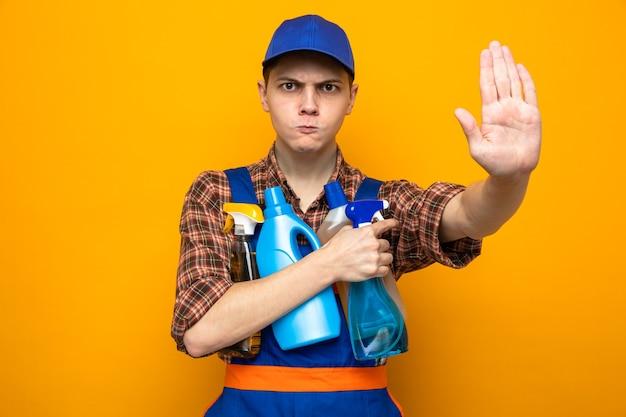 Ścisły gest zatrzymania, młody facet sprzątający ubrany w mundur i czapkę, trzymający narzędzia do czyszczenia