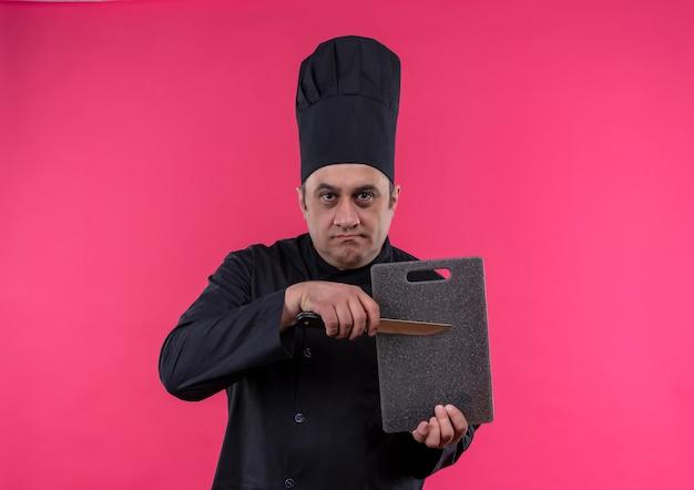 Ścisły mężczyzna w średnim wieku kucharz w mundurze szefa kuchni trzymając deskę do krojenia i nóż