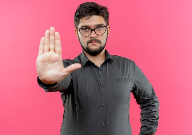 Ścisły młody biznesmen w okularach pokazujący gest stopu na różowym tle