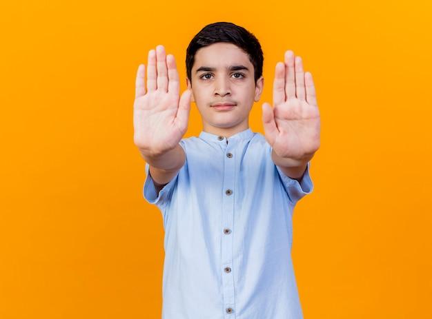 Ścisły młody chłopak kaukaski patrząc na kamery robi gest stopu na białym tle na pomarańczowym tle z miejsca na kopię