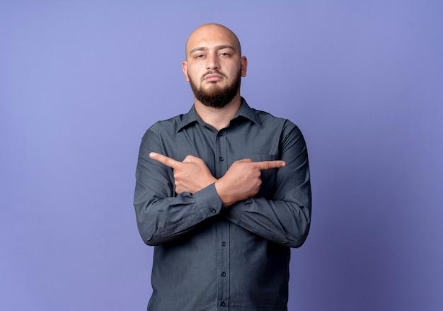 Ścisły młody łysy mężczyzna call center, wskazując na boki na białym tle na fioletowej ścianie