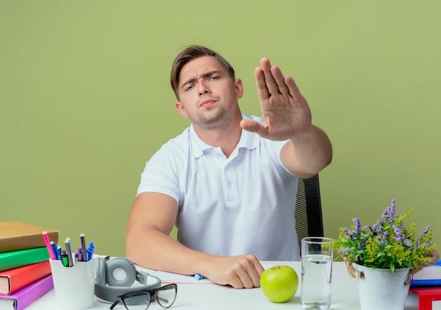 Ścisły młody przystojny student płci męskiej siedzi przy biurku z narzędziami szkolnymi pokazując gest stop na oliwkowej zieleni