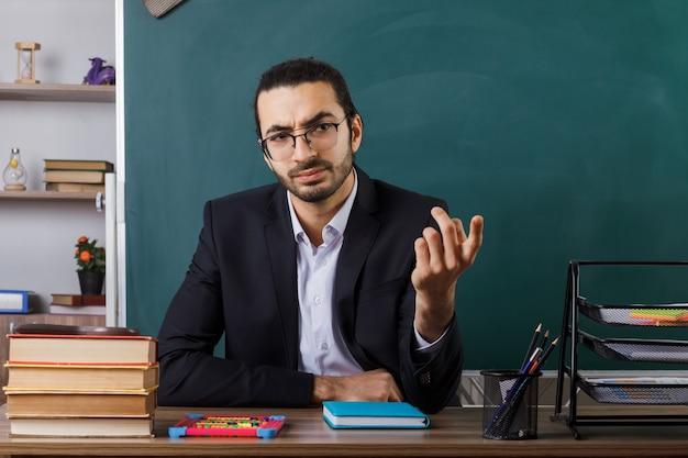 Ścisły pokaz chodź tutaj gest nauczyciel w okularach siedzący przy stole z szkolnymi narzędziami w klasie