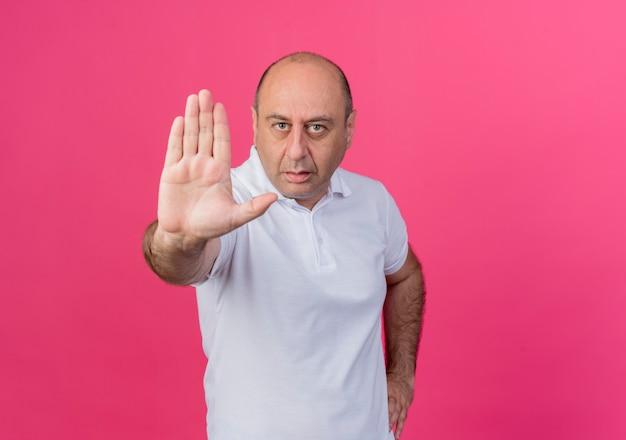 Ścisły przypadkowy dojrzały biznesmen, trzymając rękę na talii i robi gest stopu przed kamerą na białym tle na różowym tle z miejsca na kopię