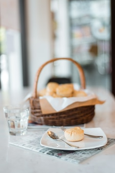 Scone na białych talerzach postawionych na marmurowych stołach