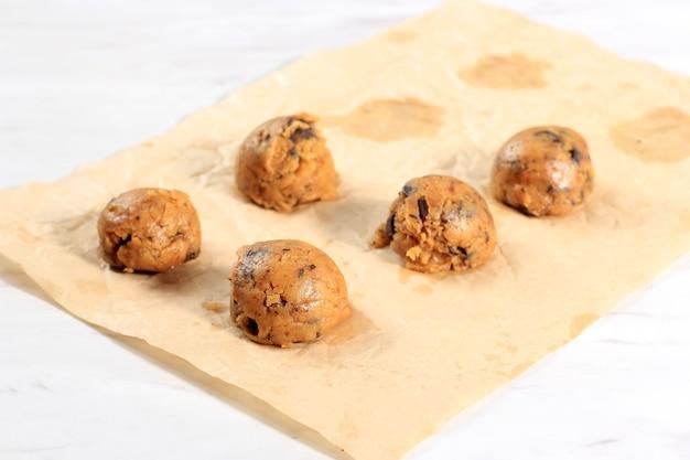 Scooped surowego ciasta chocochip cookie nad marmurowym stole. pieczenie krok po kroku. ciasto gotowe do pieczenia