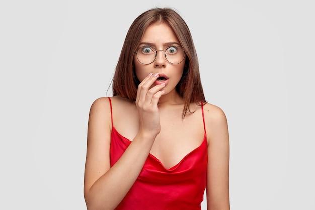 Scraed brunetka młoda kobieta pozuje przy białej ścianie