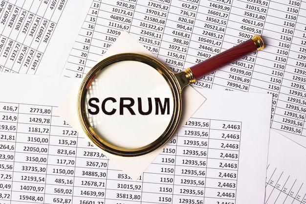 Scrum słowo przez szkło powiększające nad finansowymi dokumentami biznesowymi koncepcja nowoczesnych metod w m...