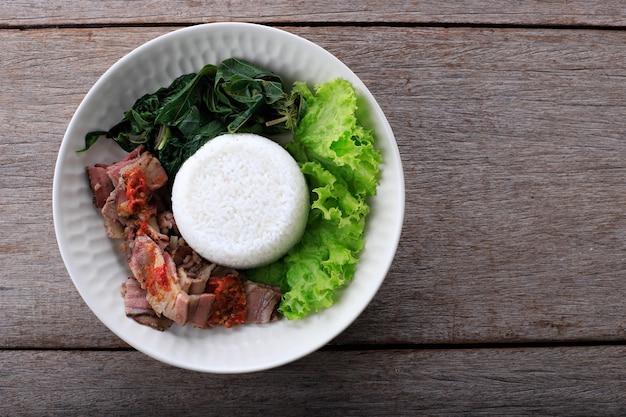 Se'i sapi lub beef sei to indonezyjska tradycyjna wędzona wołowina, podawana z gotowanymi liśćmi manioku i sambal luat lub sambal matah. typowe jedzenie z nusa tenggara w indonezji