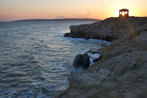Sea surfuje wielka fala na linii brzegowej i przylądek z pawilonem w oddali