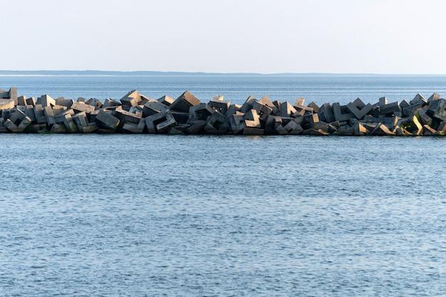 Seascape minimalizmu. podróże marzeń, miejsce. zapierający dech w piersiach widok na morze z falochronami. spokojna błękitna woda morska.