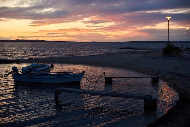 Seascape piękny wieczór o zachodzie słońca. małe łodzie motorowe zakotwiczone na brzegu w zatoce morskiej spokojna płytka woda przywiązana do molo linami na jasnym pomarańczowym pochmurnym niebie i lśniących lampach ulicznych