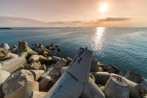 Seascape piękny zachód słońca. falochrony czworonogi na brzegu molo. statki towarowe na horyzoncie. podróżuj marzeń i motywacji
