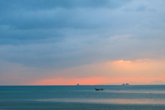 Seascape przy zmierzchem z łodzią w morzu