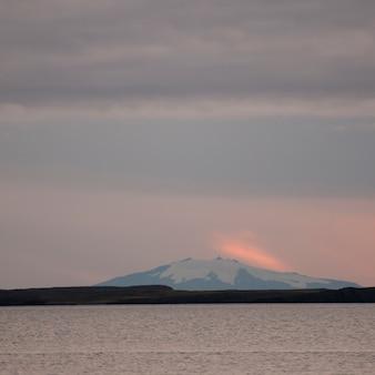 Seascape, śnieżna góra w różowym wieczór zmierzchu