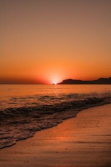 Seascape z czystym niebem i falami na zachodzie słońca