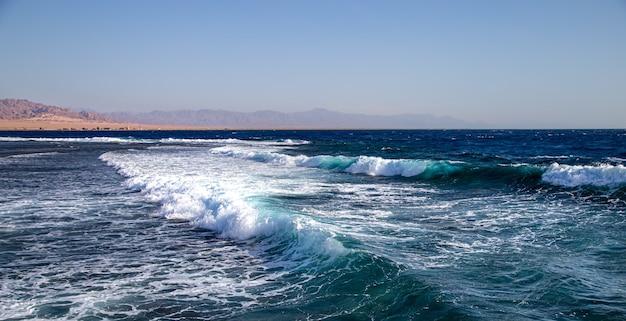 Seascape z teksturowanymi falami i górskimi sylwetkami na horyzoncie.