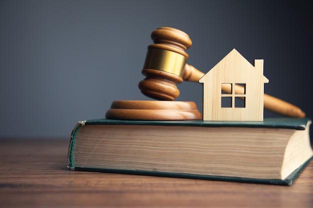 Sędzia aukcji i koncepcja nieruchomości. model domu, młotek i książki prawnicze