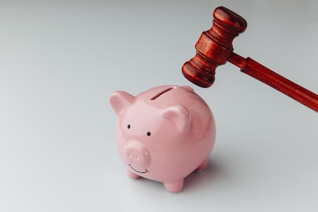Sędzia drewniany młotek i różowa skarbonka na białym tle. kredyt i koncepcja biznesowa