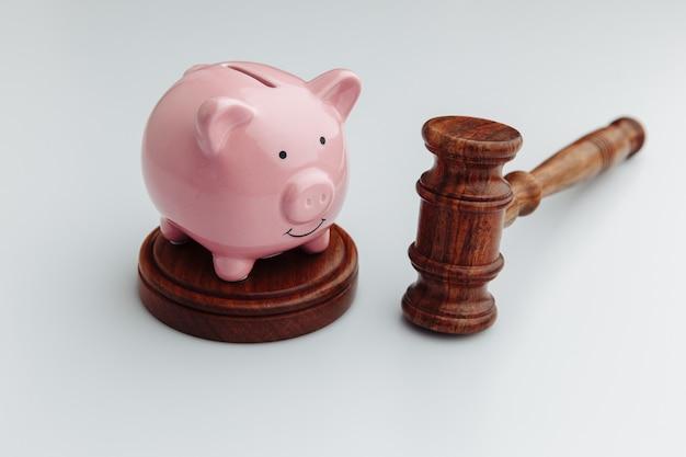 Sędzia drewniany młotek i różową skarbonkę na białym stole.