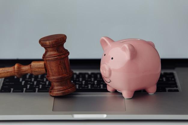 Sędzia drewniany młotek i skarbonka na laptopie.