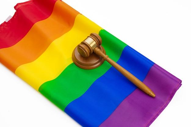 Sędzia drewniany młotek i tęczy flaga na białym tle. prawo i lgbt