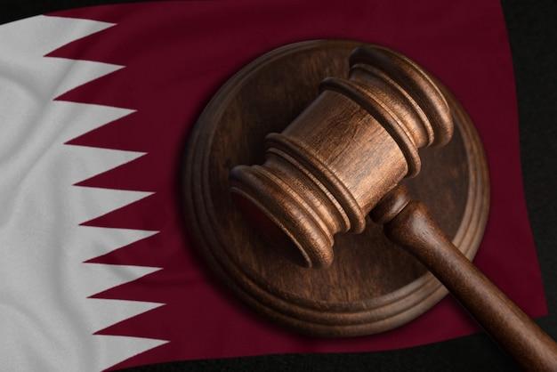 Sędzia gavel i flaga kataru. prawo i sprawiedliwość w katarze. naruszenie praw i wolności.